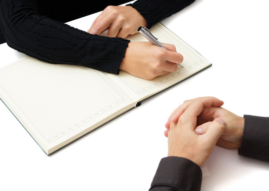 a man keeping notes while interviewing - Nursery Nurse Interview Questions And Answers